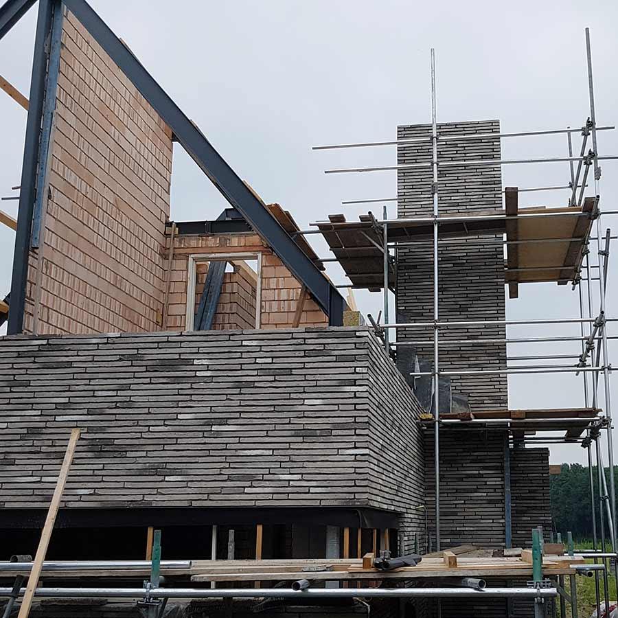 Schoorsteen in de steigers van een nieuwe woning in Nuland